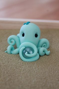 This listing is for one (1) hand sculpted polymer clay octopus. He is approximately 1.25 tall and 2 in diameter. Two of his tentacles form around a crystal clear glass marble. The rest are delicately curled. He can also be made in other colors, just send me a convo :) He would look