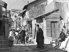 """Σκηνή από την ταινία """"Συνοικία στο όνειρο"""". Η ιστορική φτωχογειτονιά του Ασυρμάτου αποτέλεσε το σκηνικό γυρισμάτων της περίφημης ταινίας «Συνοικία στο όνειρο» του Αλέκου Αλεξανδράκη. Η ταινία έμεινε στην ιστορία για τη λογοκρισία που υπέστη και τις προσπάθειες του Αλεξανδράκη να καταφέρει να την προβάλει στον κινηματογράφο. Τα εξωτερικά γυρίσματα έγιναν στις παράγκες του Ασύρματου με φόντο την Ακρόπολη. Όπως ανέφερε ο Δ.Σ. Δεβάρης, ο Ασύρματος, ήταν «η γραφικοτέρα αθλιότης», κάτι που είχε… Time Heals All Wounds, Classic Movies, Historical Photos, Athens, Old Photos, Greece, Street View, Black And White, World"""