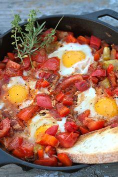 (Frigideira Pimentada de Molho Tomates c/ Ovos Fritos: 2 pimentas (pimentão vermelho), em cubos  4 tomates em cubos,  1/2 cebola picada,  2 colheres de sopa de azeite  Sal e pimenta a gosto  2 dentes de alho picados  1/2 colher de chá de alecrim picado  1/2 colher de chá de orégano, picada  4 fatias de bacon, cozido e picado  4 ovos  1 pão Artisan pão, cortada