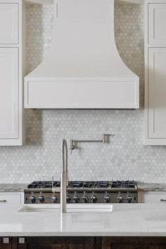 Amazing kitchen features creamy white shaker cabinets paired with grey granite countertops and a carrera marble hex backsplash.