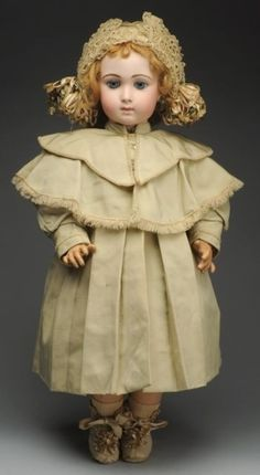 Exceptional French Long Face Jumeau Bébé Doll. Antique white cotton dress and underwear, coat from antique fabrics, lacy antique hat, shoes and socks.