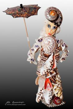 Seashell lady with umbrella figurine statue made on the natural coral base.