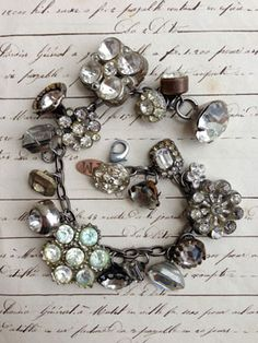 Vintage Rhinestone Button Bracelet #20 This bracelet has all vintage rhinestone buttons. There are so many different varieties and sizes, some with lacy bezels, some with clean setting and no prongs, some with gold tone settings, most with silver, all with various signs of age (which we love!)!..
