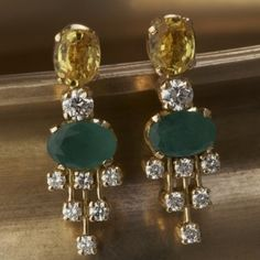 A classic pair of earrings showcasing diamonds, emeralds and citrines is handcrafted in 18k gold.