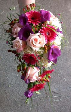 Soft pink roses, purple lisianthus, hot pink mini gerbera daisies and red hypericum berries create a beautiful cascade shape for this wedding bouquet. The loops of beargrass add further texture and interest to the bouquet.