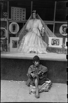 "© Henri Cartier-Bresson/Magnum Photos CHINA. Zhejiang. Hangzhou. 1949. To a man without shelter, the sidewalk is his resting place.  Behind him, the studio of a photographer, who also offers wedding gowns ""of high style and at reasonable prices""."