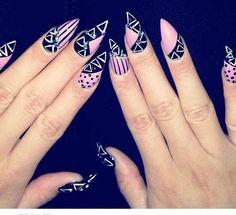 black , pink , and white tribal stiletto nails .
