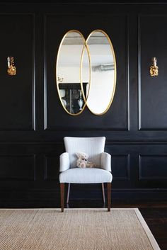 Function meets comfort in this historical design. A sleek shade of ebony covers the walls and delicate paneling for a sophisticated look. Overlapping oval golden mirror, black wall with golden sconces and white chair. ➤ Discover the season's newest designs and inspirations. Visit us at http://www.wallmirrors.eu #wallmirrors #wallmirrorideas #uniquemirrors @WallMirrorsBlog