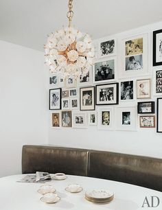 The breakfast area of magazine editor Darcy Miller Nussbaum's New York apartment features a vintage pendant light and photos hung salon style.