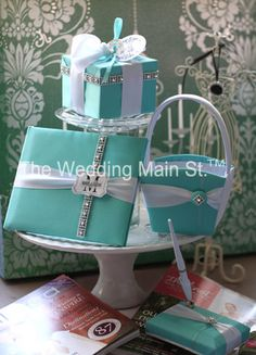 This will be the Tiffany & Co wedding ensemble. It includes a guestbook and pen, a flower girl basket, and a Tiffany box that serves to hold the rings in place of a pillow for the ring bearer.