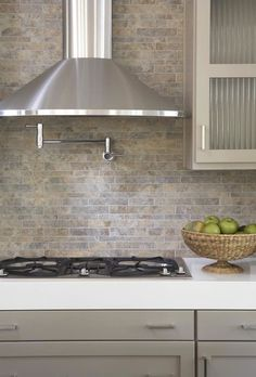 kitchens - pot filler tumbled linear stone tiles backsplash taupe gray kitchen cabinets white quartz countertops  Gorgeous modern  kitchen design  #CambriaQuartz
