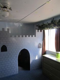 Boys' loft bed, took the bottom bunk out and faced it with plywood cut and painted to look like a castle. Underneath is their toy box and bookcase. The boys and their new sister had to share a room, so what better way to incorporate princess stuff into a boys room then make them a knight castle :o)