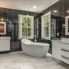 Modern en suite bathroom with heated flooring, free standing soaking tub, floor to ceiling tile, dual floating vanities and sinks, and walk-in tile shower with a glass door, multiple jets and a rain shower head. Listed for $1,350,000 in Oakton, VA by The Casey Samson Team is a Wall Street Journal Top Team in Northern Virginia.