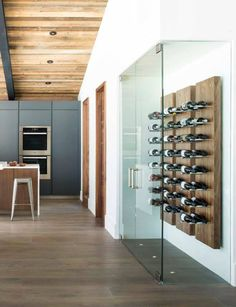 Wine Rack Ideas - Show Off Your Bottles With A Wall Mounted Display // The steel pegs contrast the wood panels and are long enough to fit two bottles of wine on pair of pegs.
