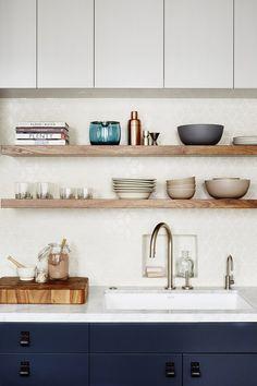 Navy kitchen cabinets, rustic wood open shelving under upper cabinets, white tile backsplash