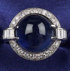 Art Deco Platinum, Sapphire, and Diamond Ring, centering a sapphire cabochon measuring 10.70 x 10.45 x 7.00mm, surrounded by baguette, triangular, and single-cut diamonds