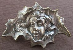 Antique sterling silver Art Nouveau Unger Brothers Christmas brooch, girl's head in a holly leaf