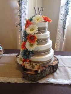 Rustic style wedding cake with white, orange, and teal flowers and burlap/twine wrap.