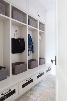 Linear slate tiles lead to white beadboard open mudroom lockers fitted with oil…