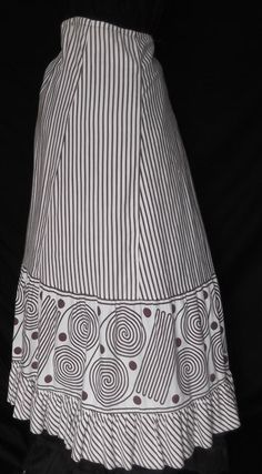 This petticoat dates to the 1890's and is fashioned of white cotton with a brown stripe and bold swirl print.