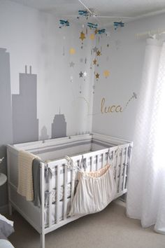 To personalize the newborn's sleeping area the babies name was painted on the wall using metallic paint pens. This common detail of in a nursery could have been done with store bought wooden letters or pre-existing decal lettering. Instead, considering the position near the cityscape mural and under the starry mobile sky the lettering was custom designed and presented as if it is skywriting.