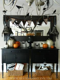 Such a cute but classy, if halloween can be classy, way to decorate for halloween! I also like the idea of the punch paper circle garland hanging from the branches...could work for any holiday as well as the fabric and felt penant banner. CUTE!