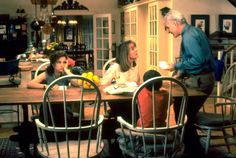 Starring Diane Keaton as Nina Banks and Steve Martin as George Banks in a remake of this classic film, the couple's traditional Colonial home was a hit with design-minded viewers. The kitchen features Windsor chairs around a farm-style table, butcher-block countertops, and glass-fronted upper cabinets. Beyond the table, a pot rack hangs above an open island — the gathering spot for many family conversations, including the scene where Annie (Kimberly Williams) opens the wedding gift of a…