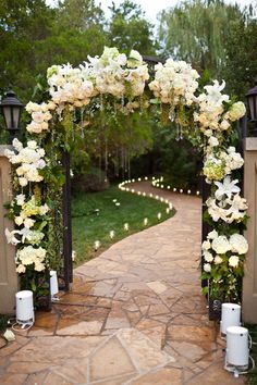Very similar to this with sting lights on the arch, and gold sticks and petal lined aisle with candles