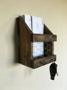 Rustic mail and key holder. Distressed. Chicken wire front and two black hooks.  Stain is provincial by min wax.  Approx. Dimensions 71/2 Width. Height 95/8. Finished screwed together. Very rigid.  Installation: Simply screw to the wall. Note: Naturally, reclaimed wood has imperfections, including its texture, weathered appearance, nail holes, and knots. We are selective with the pieces we choose to work with, ensuring the quality and character of the product are at its best.