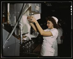 A 1940s nurse examines a pair of blood transfusion bottles at Baxter Lab., Glenview, Ill, during the 1940s ~