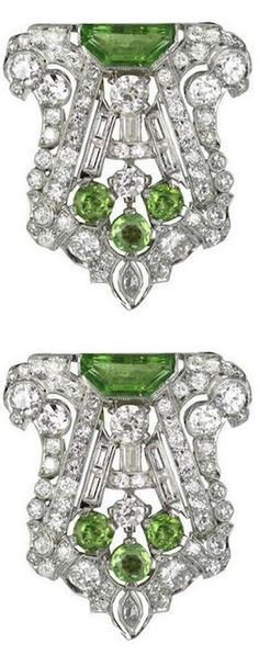 """*Pair of Art Deco Peridot Diamond Dress Clips,Each Art Deco dress clip of this pair is designed as an openwork geometric plaque with circular and baguette-cut diamonds, set with half-moon-shaped and circular-cut peridots, the diamonds altogether weighing approximately 8.18 total carats, mounted in platinum, the clips can also be combined to be worn as a single ornate brooch. 1.4"""" length and 1.1"""" width at the widest point.:"""