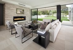 Minimalist style enclosed fireplace extends from the wall. Seamless glass windows and door lead out into the backyard.