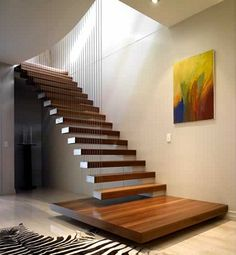 Open riser staircase with wooden treads supported by wall and cable.