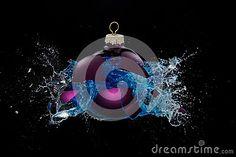 A purple bauble bursts splashing around blue liquid