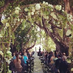 Wedding ceremony under the banyan trees. A romantic floral arch was created for the entrance to the moss lined aisle lined with white pillar candle filled lanterns and flowers.