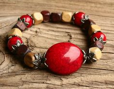 This bracelet features deep red-marsala crackle/marbled plastic beads, wooden accent beads, and a focal bead surrounded by antiqued silver, metal leaf spacer beads.  This bracelet with it's Indie-Boho flair is the perfect unique touch to complete any outfit for a great summer look.