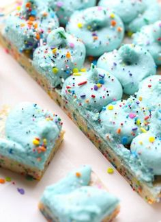 Unicorn Bars are buttery, sugar cookie bars loaded with rainbow sprinkles and topped with clouds of blue buttercream!