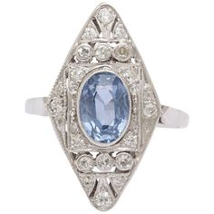 Art Deco Ceylon Sapphire and Diamond Ring. This lovely Art Deco ring had a central light blue oval 5 x 8 mm faceted sapphire. The center stone is surrounded by a delicate pierced Art Deco design, finely bezel and pave set white diamonds.