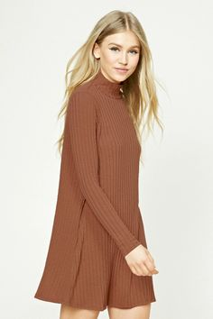 A ribbed knit dress featuring a turtleneck, swing silhouette, and long sleeves.