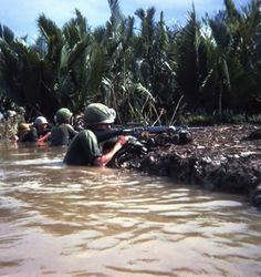 Caught in midst of canal crossing, members of 3rd Plt. CoB 2/3 199th Light Inf. Bde. return fire.  Mekong Delta, s/w of Saigon 1967.