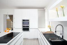 Bílá elegance. Čistota. Otevřený prostor a světlo. Tak všechno tohle se dá říci o bílých kuchyních. Pakliže k tomu přibude správná kombinace úchytové profily a čela v bílém lesku, pracovní deska z umělého kamene, tak se dá očekávat krásná kuchyň. Výsledný efekt dokáží umocnit správně vybrané kuchyňské spotřebiče. Netradičně tvarovaná indukční varná deska s varnými zónami vedle sebe s černým sklokeramickým povrchem a černý granitový dřez, naproti desky, působí vskutku harmonickým dojmem. V…