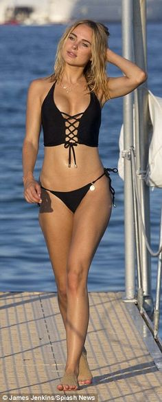 All eyes on her: Clad in a sexy black two-piece from her eponymous collection, the 26-year-old starlet oozed glamour as she enjoyed a relaxing stroll along the coast