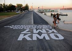 The goal of the Bikeway Belém project was not only to define and provide wayfinding guidance for the new bike route along the river Tagus in the center of Lisbon, but to energize the diverse urban spaces that it traverses. Environmental Graphics, Environmental Design, Contemporary Landscape, Urban Landscape, Contemporary Architecture, Road Markings, Landscape And Urbanism, Landscape Design, Bike Path