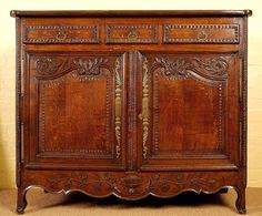 18th Century French oak carved buffet.    The cleated top housing horizontal planks above three drawers with angled chip carving and the original shaped brass handles. The doors have fielded panels with exceptional carvings, above a shaped apron havinag a carved urn with flowers flowing.    Note: Generous chestnut interior and original lock and brasswork, good overall patina.    1770 - 1820