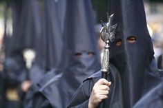"""A """"nazareno"""" is taking a break during a processional march of the """"Viernes Santo"""" in Málaga, Spain."""