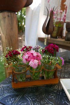 Deko-Idee für den Tisch. Egal, ob im Garten oder drinnen. Diese sechs Vasen im Rost-Look mit bunten Blumen sind ein Hingucker auf dem Tisch. Die Tischdeko passt zum Beispiel auf Holztischen im Garten. Auf einem Untersetzer platziert oder einfach nur so. Vorsicht: Rostgefahr bei Regen. Mit weißem Schleierkraut und rosa Nelken kombiniert ist das eine schöne Tischdeko für den Sommer.
