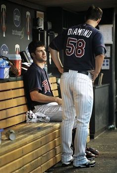 Minnesota Twins starting pitcher Scott Diamond (58) talks with catcher Joe Mauer in the dugout after giving up the first two hits against the Cleveland Indians in the fifth inning of a baseball game on Friday, July 27, 2012, in Minneapolis.