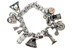 """Silver chain bracelet with 10 charms including a working hourglass, birthday cake with working pop-up candles, tri-corner hat, Eiffel Tower, drama masks, bicycle, telephone, wishing well, bell and typewriter eraser. Charms, 1""""Sq."""