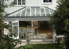 Wide opening doors lead from conservatory kitchen extension in near Richmond South West London Conservatory Extension, Conservatory Kitchen, Exterior Door Colors, Exterior Doors, Glass Door Knobs, Glass Front Door, Kitchen Pantry Doors, Roof Lantern, Kitchen Dining Living