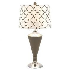"""Crafted of glass with an iron base, this table lamp features a white drum shade with a quatrefoil motif.   Product: Table lampConstruction Material: Glass, iron and fabricColor: Taupe and whiteFeatures: Quatrefoil patternDimensions: 29.75"""" H 15"""" Diameter"""